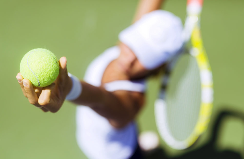 Woman taking a tennis serve